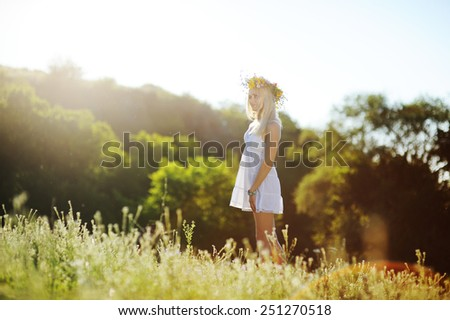 girl in a white sundress and a wreath of flowers on her head against a background of trees. - stock photo