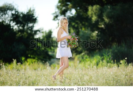 girl in a white sundress and with a wreath of flowers in hand on background of trees - stock photo