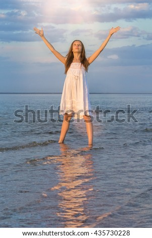 Girl in a white sundress standing in the water at the beach with their hands raised in the last rays of the sun and says goodbye to the setting sun - stock photo