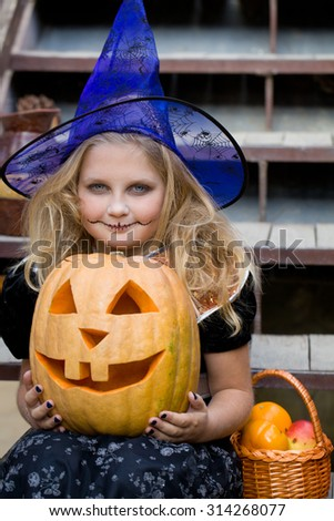 girl in a witch costume with halloween pumpkin on holiday