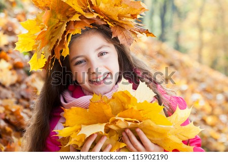 girl in a wreath of maple leaves with autumn bouquet