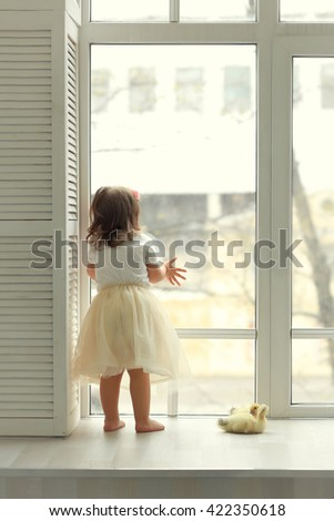 girl in a yellow skirt looks out the window beside the ducklings - stock photo