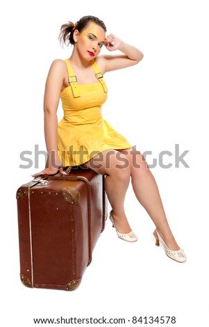 Girl in a yellow summer dress with a huge antique suitcase poses on a white background
