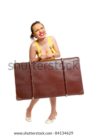 Girl in a yellow summer dress with a huge antique suitcase poses on a white background - stock photo
