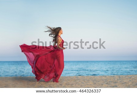 Girl in airy dress running along the beach