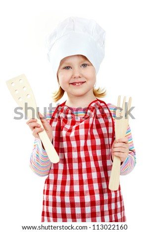 Girl in an apron and cook cap holding wooden kitchen tools - stock photo