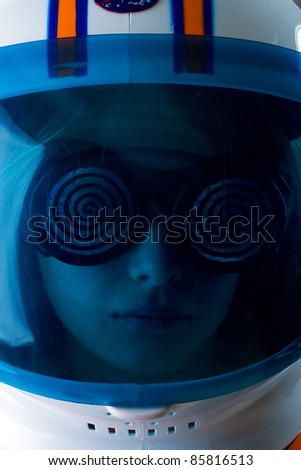 Girl in an astronaut helmet with space aged glasses on.