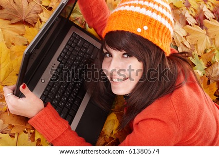 Girl in autumn orange leaves with laptop.  Outdoor. - stock photo