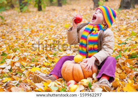girl in autumn park eat apple
