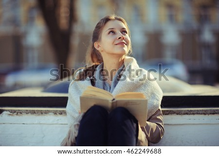 girl in autumn park with a book