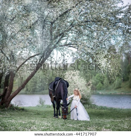 Girl in beautiful white dress with black horse in blossom garden