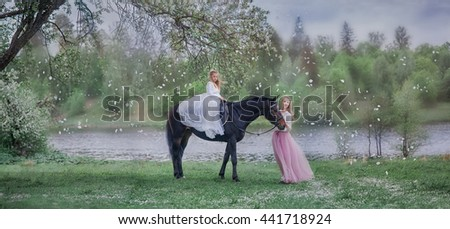 Girl in beautiful white dress with mother on black horse in blossom garden  - stock photo