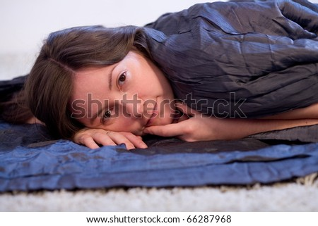 Girl in bed, covered with a blanket.