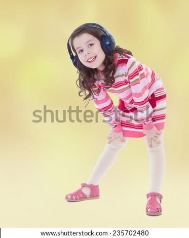 Girl in big black headphones listening to music.Summer background. - stock photo