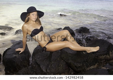 girl in bikini and hat lounging on lava rocks by the ocean - stock photo