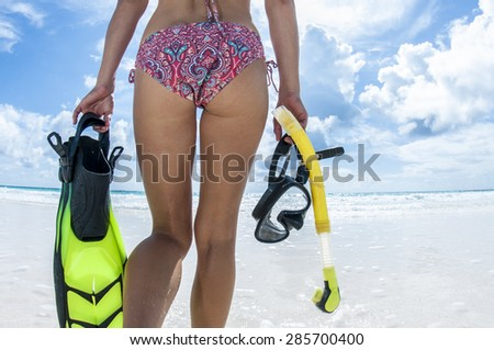 Girl in Bikini on the beach holding mask, fins and snorkel