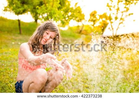 Girl in bikini sitting at the sprinkler, summer garden - stock photo