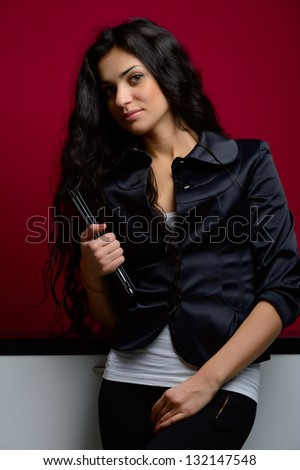 girl in black and white dress with tablet on red background