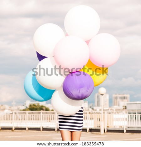 girl in black and white striped short dress and white high top sneakers hides in bunch of multicolored balloons - stock photo