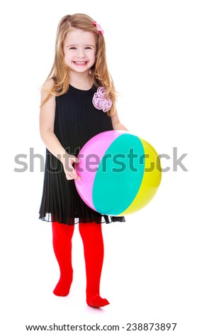Girl in black dress holding a ball. Isolated on white background studio photo.
