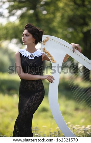 girl in black dress playing the harp white - stock photo