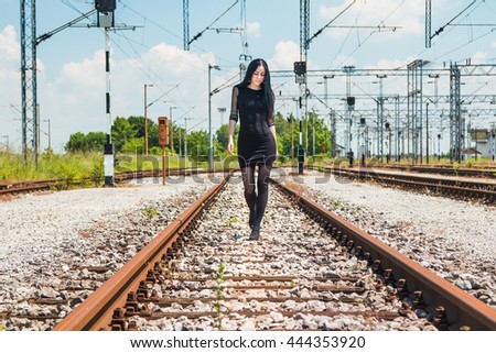 Girl in black dress walking on rail tracks - stock photo