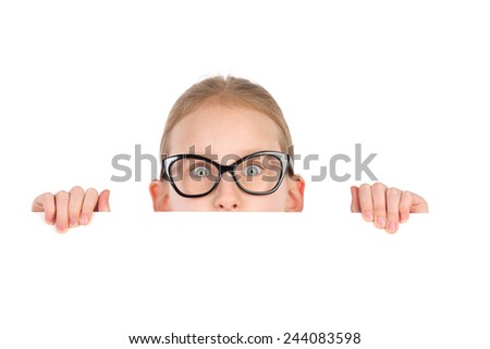 Girl in black glasses peeking behind white placard and looking at camera. Studio portrait isolated on white.