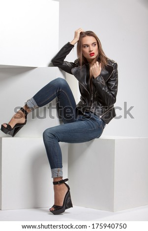 girl in black leather jackets, biker jacket posing in studio on large white cubes - stock photo