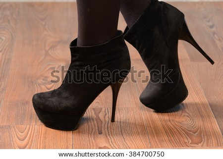 Girl in black suede boots with high heels on the wooden floor - stock photo
