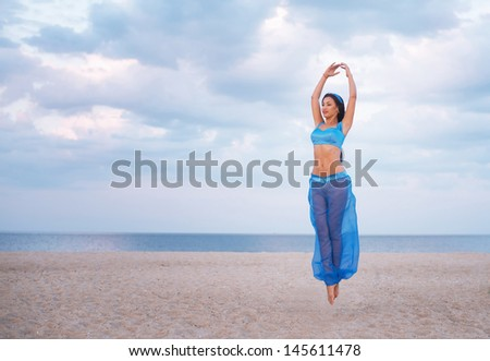 Girl in blue belly dance costume in the air - stock photo