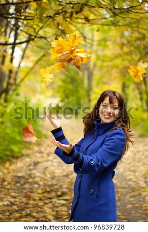 Girl in blue coat throw up yellow leaves - stock photo