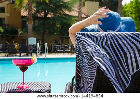 Girl in blue hat with cocktail drink by the pool