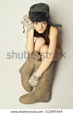 Girl in boots and a fur hat, winter - stock photo