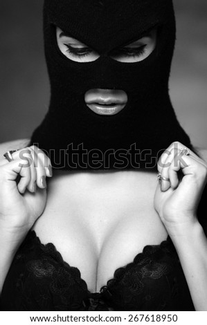 girl in bra and balaclava - black and white photo in studio of a psycho girl - stock photo