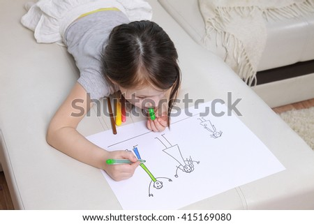 Girl in bright clothing draws a picture of the family. Light room