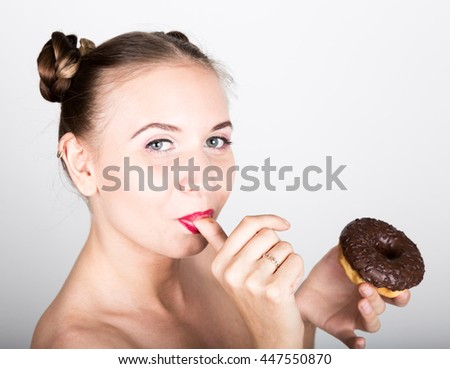 girl in bright makeup eating a tasty donut with icing. Funny joyful woman with sweets, dessert. dieting concept. junk food. girl licking her fingers - stock photo