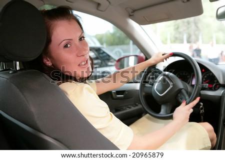 girl in car keeps steering wheel - stock photo