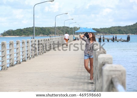 Girl in checked shirt with notebook moleskin in hands standing on bridge in the sea, bay bridge, girl dreaming