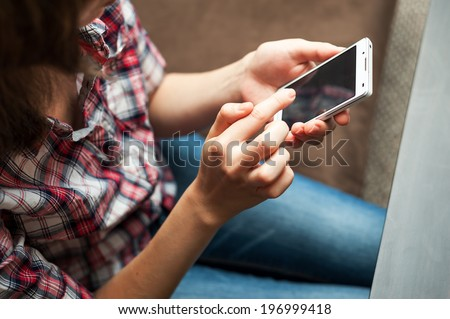 Girl in checkered shirt taping in cell phone - stock photo