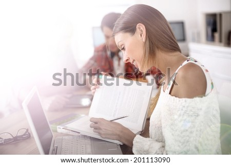Girl in class studying with laptop and school book - stock photo