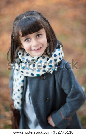 girl in coat and scarf smiling