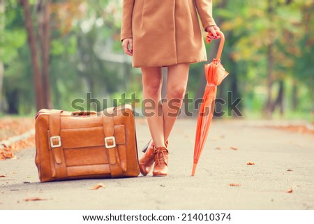 Girl in coat with umbrella and suitcase in the park. - stock photo