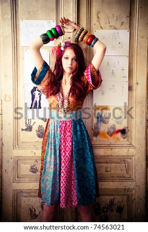 girl in colourful summer dress and lot of bracelets stand in front door - stock photo