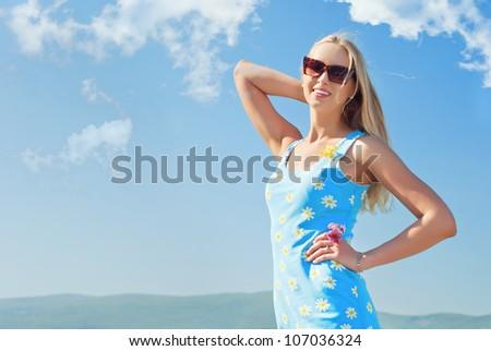 girl in dark glasses against the blue sky - stock photo