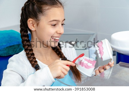 Girl in dentist's office shows how to brushing your teeth - stock photo