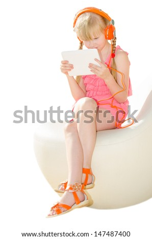 Girl in design armchair holding tablet PC and watching video in orange headphones isolated on white - stock photo