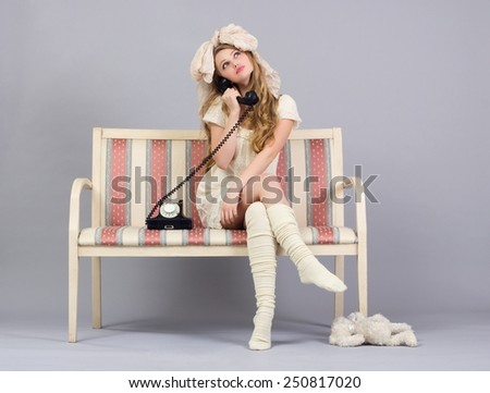 Girl in doll clothes speak retro phone sitting on a sofa. - stock photo