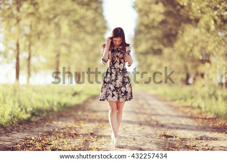 Girl in dress on the summer road - stock photo