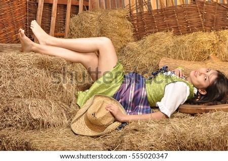 Girl in dress resting in the hay barefoot