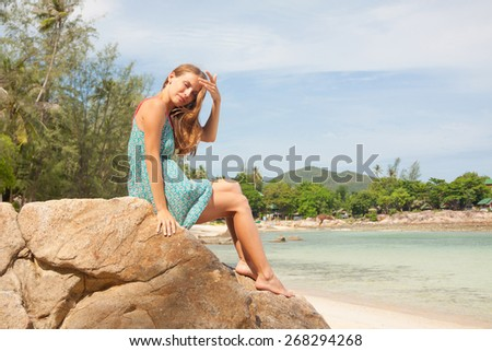 girl in dress sitting on a stone by the sea - stock photo